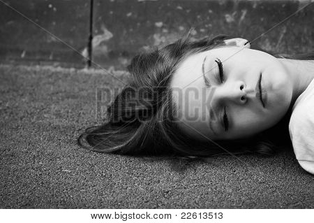 Portrait Of Sleeping Young Girl Lying On Asphalt. Black And White Photo