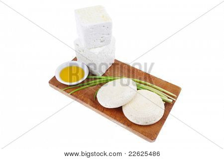 dairy product : fresh raw white soft greek feta cheese cubes and round on wooden plate isolated over white background