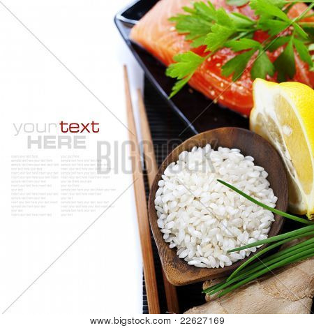 traditional asian ingredients (Fresh salmon steak filet, uncooked rice, ginger, lemon,   and chopsticks) over white with sample text