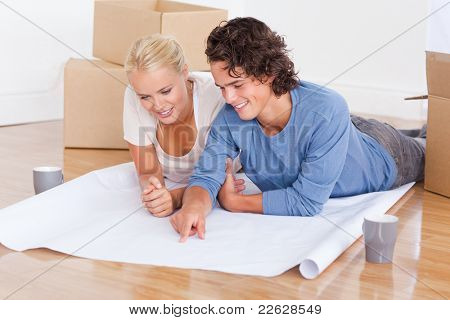 Young couple getting ready to move in a new house while lying on the floor