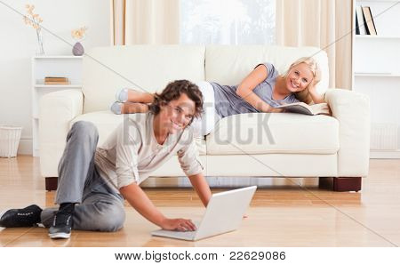 Man with a notebook while his girlfriend is holding a book looking at the camera