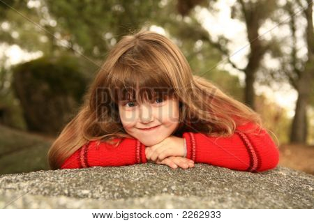 Shy Sweet Chilld Outdoors On A Rock