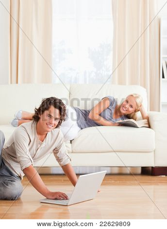 Portrait of a man with a notebook while his girlfriend is with a book in their living room