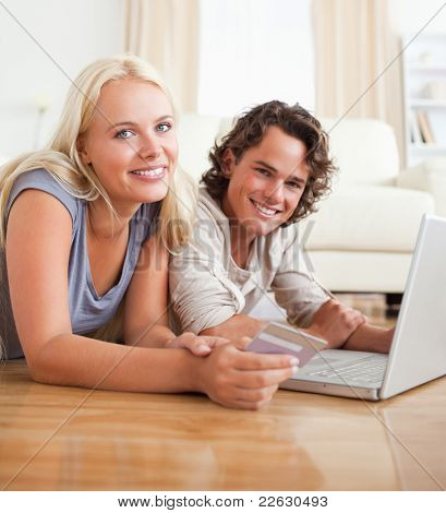 Cute couple booking their holidays online in their living room