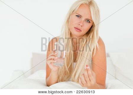 Blonde woman taking a pill in her bedroom