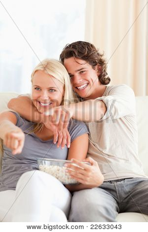 Portrait of a couple watching TV while eating popcorn in their living room