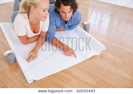 Young couple looking at their future room on a plan while lying on the floor