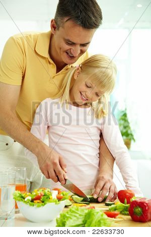 Portrait of happy father and daughter cooking vegetable salad in the kitchen