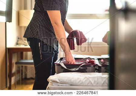 poster of Man Packing Suitcase For Vacation. Person Putting Clothes To Baggagge In Hotel Room Or Home Bedroom.