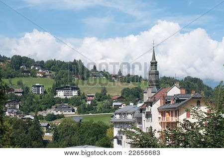 The Church Of Saint-gervais-les-bains And The Building On The Mountain