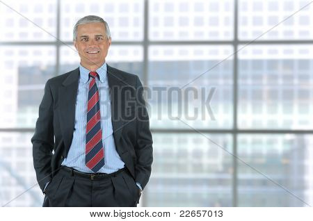 Smiling middle aged business man isolated on white with his hands in pants pockets. Vertical Format standing in front of large window of modern office building.