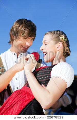 Young and beautiful couple in traditional Bavarian Tracht - Dirndl and Lederhosen - embracing each other on a fair like a Dult or the Oktoberfest eating traditional sugar apple