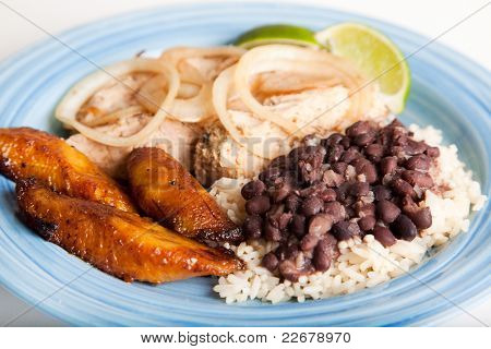 Traditional Cuban meal, of roast pork, black beans and rice, and sweet fried plantains.  Focus on the beans and rice, and the plantains.