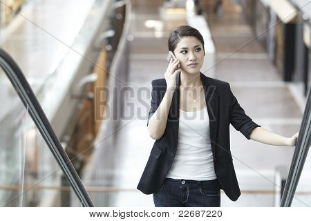 Business Woman Using A Mobile Phone On An Escalator