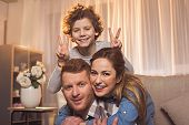Portrait Of Happy Unshaven Husband And Glad Wife With Laughing Curly Child Looking At Camera. Family poster