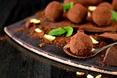 Chocolate Truffles Covered With Cacao Powder, Pistachio Nuts, Chocolate And Mint On A Dark Wooden Bo poster