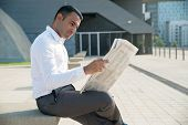 Smiling Young Businessman Interested In News Enjoying Morning Newspaper. Content Latin Male Manager  poster