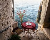 A Beautiful Summer View Of A Sea From A Little Romantic Patio. There Are A Table With A Glass And A  poster