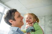 Father With The Little Daughter. The Young Man Holds The Little Fair-haired Girl On Hands. He Looks  poster