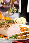 stock photo of roasted pork  - Delicious garlic thyme roast pork loin is ready for dinner in middle of fall arrangement table and two glasses of red wine - JPG