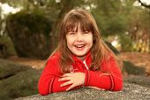 Laughing Child With Arms Crossed Outdoors On A Rock poster