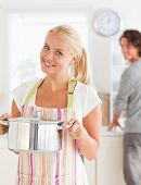 stock photo of italian food  - Portrait of a woman posing while her fiance is washing the dishes in their kitchen - JPG