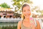 Asian tourist woman eating ice cream pop stick in Beijing city, China. Asia summer travel vacation.  poster