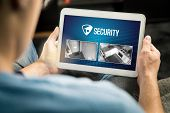 Man Using Home Security System And Application In Tablet. Watching Protection Camera Live Footage In poster