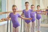 Kids Practicing Ballet At Ballet Class. Young Smiling Ballerina Standing In Pose At Ballet Barre. poster