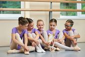 Young Ballerina With New Ballet Slippers. Group Of Young Ballet Dancers Sitting On Floor During A Br poster