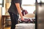 Man Packing Suitcase For Vacation. Person Putting Clothes To Baggagge In Hotel Room Or Home Bedroom. poster