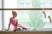 Beautiful Ballet Girl In Pink Leotard. Cute Young Ballerina Sitting On Window-sill And Looking At Po poster