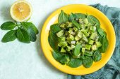 Vitamin Vegetarian Salad With Avocado, Kiwi And Spinach On Yellow Plate. Dressed With Sauce Of Lemon poster
