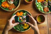 Vegetarian Indian Cuisine. The Man Takes A Photo On His Smartphone Dishes With Rice, Ogriks, Spinach poster
