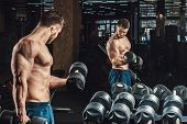 Good Looking Young Man Lifting Dumbbells And Working On His Biceps In Front Of A Mirror Looking On H poster