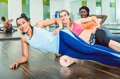 Beautiful fit woman smiling while wearing blue fitness sleeveless top and leggings during group work poster
