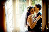The Gorgeous Newlywed Couple Is Tenderly Hugging Near The Old Open Window. The Handsome Groom Is Sof poster