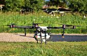 Agriculture Drone, Photo Image Of Agriculture Drone Carry A Tank Of Liquid Fertilizer Parking On Gre poster