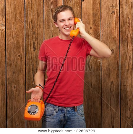 portrait of a young man talking with a vintage telephone against a wooden wall