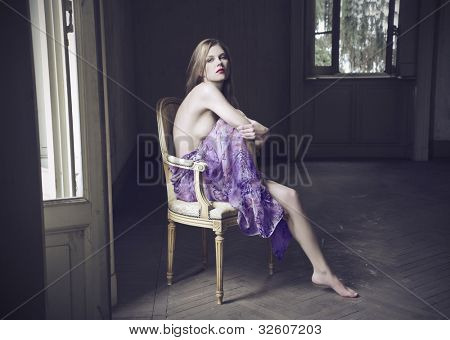 Beautiful woman sitting on an antique chair in an empty room