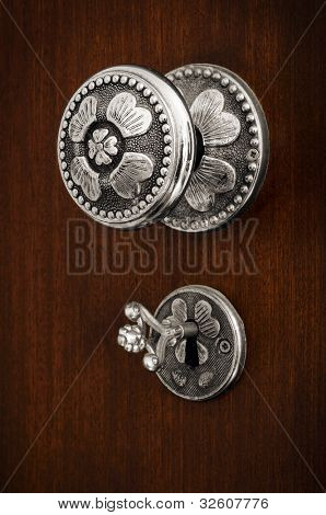 Old silver Doorknob and key on a brown wooden door