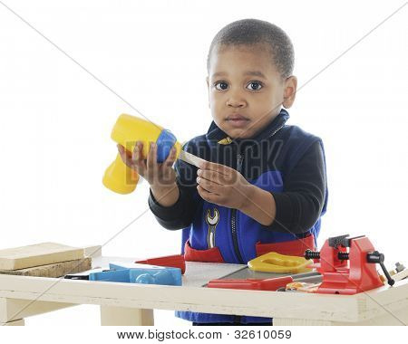 Closeup image of an adorable toddler playing carpenter with plastic tools on a work bench.  On a white background.