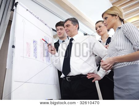 Senior male business man giving a presentation at a  meeting at modern light office on a table board