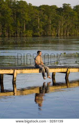 Man Fishing Of A Dock