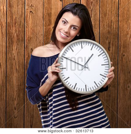 portrait of a young woman holding a clock against a wooden wall
