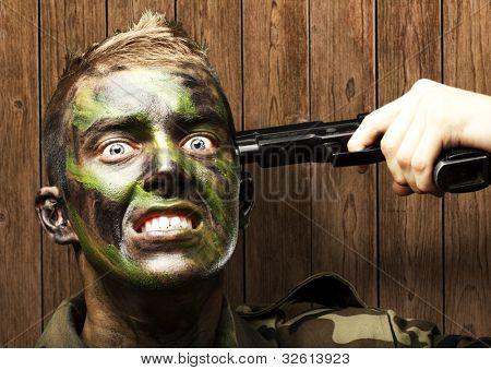 retrato de um suicídio de comiting do jovem soldado contra uma parede de madeira