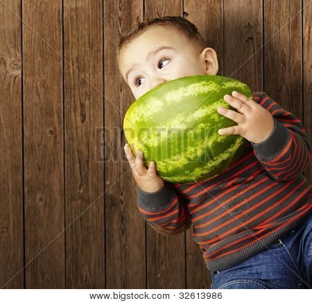 portrait of a handsome kid holding a watermelon and eating it against a wooden background
