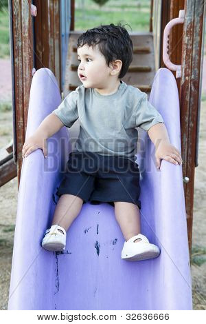 Caucasian baby boy playing on sliding board
