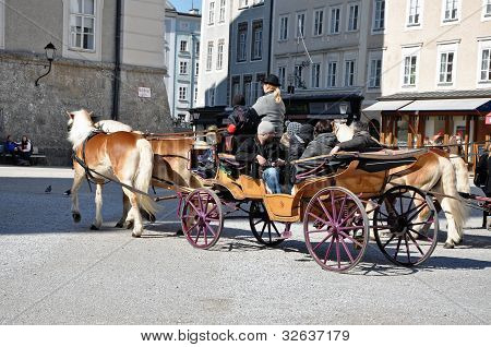 Horse driven carriage with tourists in Salzburg