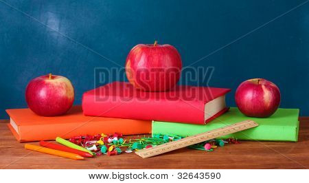 Composition of books, stationery and an apples on the teacher's desk in the background of the blackboard
